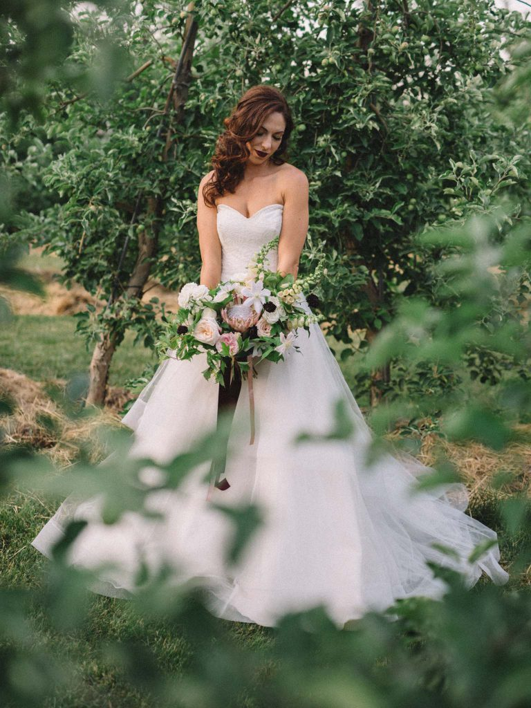 Beautiful bride with bouquet at Orchard Wedding