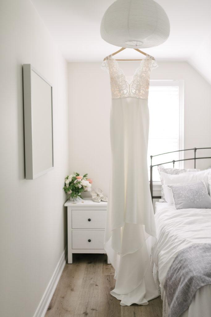 wedding dress hanging in white room