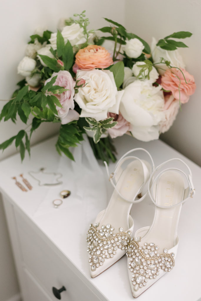 white peach bridal bouquet with shoes and jewelry