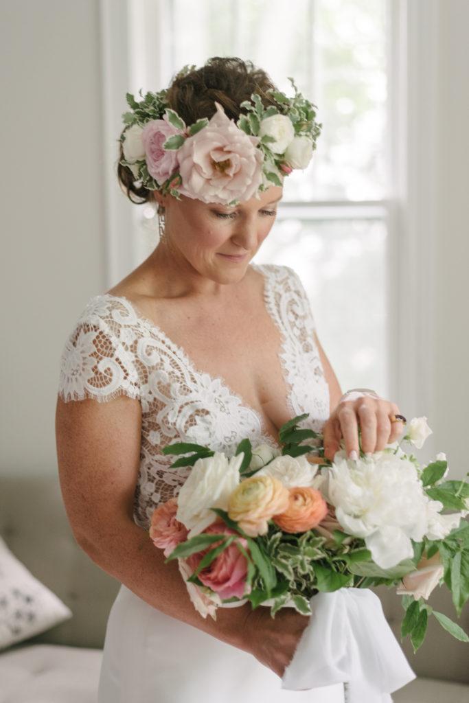 bride in flower crown looking at bridal bouquet